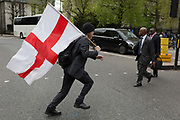 A patriotic man runs across the road carrying the English flag on St Georges Day the the streets of the capitals financial district aka The Square Mile, on 23rd April, City of London, England.