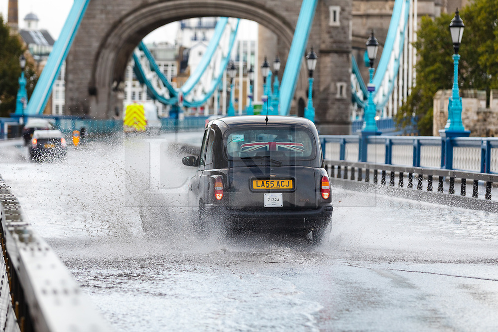 © Licensed to London News Pictures. 06/10/2019. London, UK. A taxi cab drives through flooding and excess surface water on Tower Bridge this morning following heavy rain and wet weather in the capital last night. Weather forecasts predict that most of the UK will be experience heavy rain and storms during the next few days. Photo credit: Vickie Flores/LNP