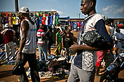 A man in the foreground checks a mobile phone as other street sellers sell both donated and imported clothes in a busy market area in Bangui.