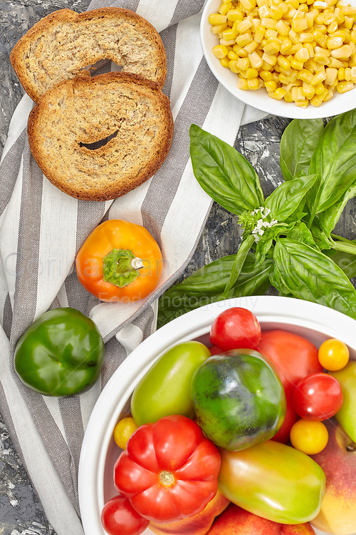 Healthy ingredients mix with various types of tomatoes, bell peppers, corn, basil and apulian bread called frisella.