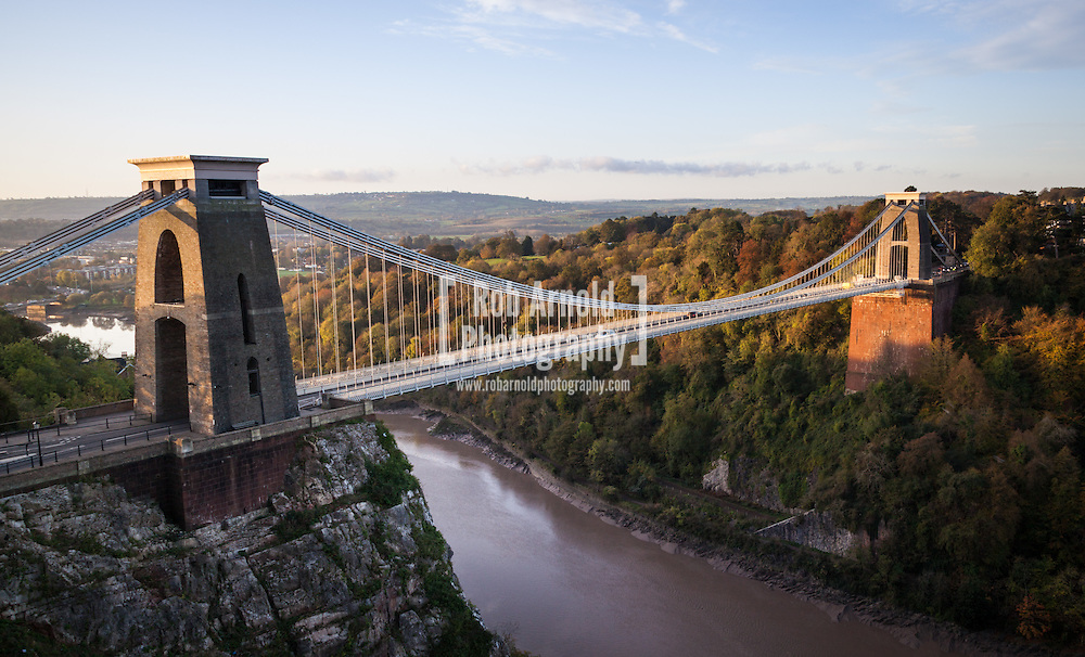 Morning autumn light shines on Brunel's Clifton Suspension Bridge, which spans the Avon Gorge in Bristol, England.