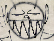 close up of a big smiling graffiti portrait on a gray wall