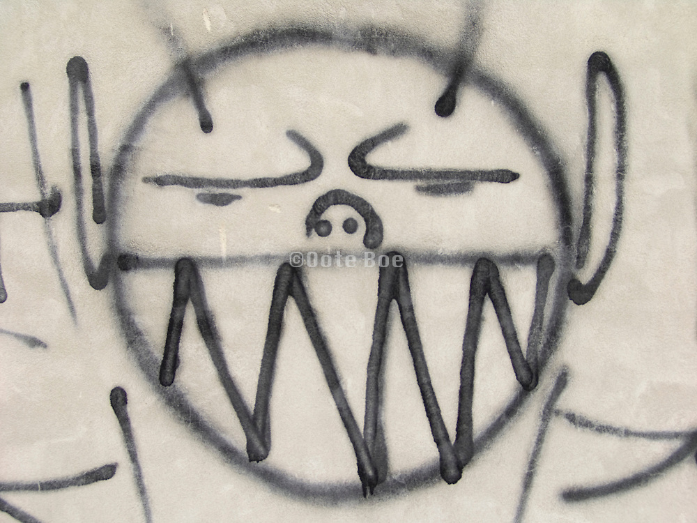 close up of a big smiling graffiti portrait on a gray wall