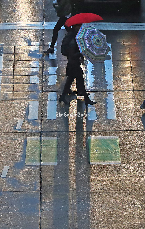 Pedestrians cope with the rain and wind recently at Sixth Avenue and Pine Street in downtown Seattle. (Greg Gilbert / The Seattle Times)