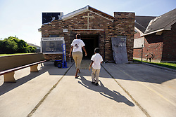 26 August 2015. New Orleans, Louisiana. <br /> Hurricane Katrina revisited. <br /> Disciples of Christ Christian Fellowship Ministry. <br /> A mother and child enter the church as furniture is delivered.<br /> Photo credit©; Charlie Varley/varleypix.com.