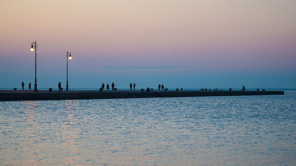 People strolling on the Molo Audace in Trieste at sunset.