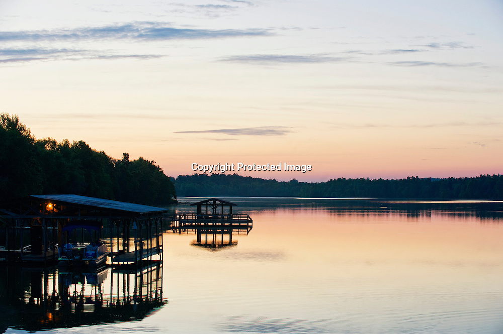 Boat docks are silhouetted against the rising sun on Lake Fayetteville in Fayetteville, Arkansas.
