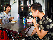 """14 FEBRUARY 2019 - SIHANOUKVILLE, CAMBODIA:  Men who work for Chinese enterprises in Sihanoukville eat lunch in a Chinese noodle shop near their apartment building. There are thousands of Chinese workers in Sihanoukville who work to support the casino and hotel industry in the town. There are about 80 Chinese casinos and resort hotels open in Sihanoukville and dozens more under construction. The casinos are changing the city, once a sleepy port on Southeast Asia's """"backpacker trail"""" into a booming city. The change is coming with a cost though. Many Cambodian residents of Sihanoukville  have lost their homes to make way for the casinos and the jobs are going to Chinese workers, brought in to build casinos and work in the casinos.      PHOTO BY JACK KURTZ"""