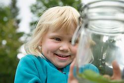 Small blonde girl collecting snails in jam-jar