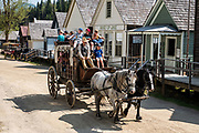 Kids ride a horse-drawn stagecoach, in Barkerville Historic Town & Park, British Columbia, Canada. Historically the main town of the Cariboo Gold Rush, Barkerville is now the largest living-history museum in Western North America. The town was named after Billy Barker from Cambridgeshire, England, who struck gold here in 1861, and his claim became the richest and the most famous. This National Historic Site nestles in the Cariboo Mountains at elevation 1200m (4000ft), at the end of BC Highway 26, 80 kilometres (50 mi) east of Quesnel. Gold here was first discovered at Hills Bar in 1858, followed by other strikes in 1859 and 1860. Wide publication of these discoveries in 1861 began the Cariboo Gold Rush, which reached full swing by 1865 following strikes along Williams Creek.
