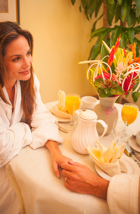 """A couple hold hands on the breakfast table in their room at The Fisher Island Club and Resort<br /> <br /> To see detailed captions for this gallery, click on a thumbnail, and then click on the """"+"""" and """"i"""" buttons that appear at lower left of the image."""
