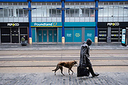 As the third national coronavirus lockdown continues, some people are still out and about but the streets remain eerily empty, like here on Corporation Street as a man walks his dog wearing a face mask on 18th January 2021 in Birmingham, United Kingdom. Following the recent surge in cases including the new variant of Covid-19, this nationwide lockdown, which is an effective Tier Five, advises all citizens to follow the message to stay at home, protect the NHS and save lives.