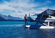 Backcountry Park Ranger Fred Hirschmann on floats of Lake Clark National Park's Cessna 185, Lachbuna Lake, Lake Clark National Preserve, Alaska.