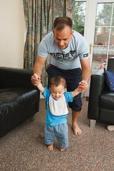 Father teaching son to walk.