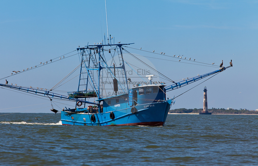A shrimping boat works the waters along Morris Island in Charleston, South Carolina with the Morris Island Lighthouse in the background.