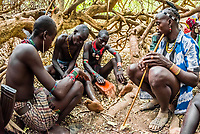 Hamer tribe people at a bull jumping ceremony, which is a rite of passage to initiate a boy into manhood. The men are being painted up to participate in the ceremony. Omo Valley, Ethiopia.