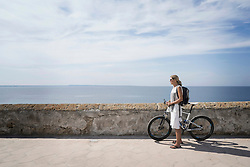 Side profile of mature woman standing with mountain bike on harbour wall, Gallipoli, Puglia, Italy