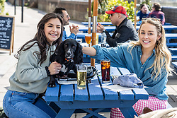 Licensed to London News Pictures. 12/04/2021. London, UK. Pub goers (left) Gabriella Lucena 24 and Gabrielle West 28 with 1 year old Lola a Cocker Spaniel enjoy a pint and a soft drink along the Thames at Hammersmith, West London for the fist time in months as pubs and shops across England welcome back customers after Covid-19 restrictions were lifted today. Prime Minister Boris Johnson announced last week that non-essential shop, restaurants with outside seating , hairdressers and gyms can reopen today after 4 months of Covid-19 lockdowns. Photo credit: Alex Lentati/LNP