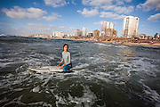 Sabah Abu Ghanem, 14, waits for a wave on a slow surf day.