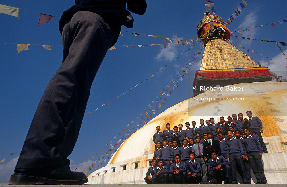 Young Nepali boys pose for a group photo beneath Kathmandu's Boudhanath Stupa after recruitment into the British Gurkhas. The recruitment test for the Gurkha Regiment is part of a tough endurance series to find physically perfect specimens for British army infantry training. For example they will need to perform 25 straight-kneed sit-ups at a 45° slant both within 60 seconds to pass. 60,000 boys aged between 17-22 (or 25 for those educated enough to become clerks or communications specialists) report to designated recruiting stations in the hills each November, most living from altitudes ranging from 4,000-12,000 feet. After initial selection, 7,000 are accepted for further tests from which 700 are sent down here to Pokhara in the shadow of the Himalayas. Only 160 of the best boys succeed in the journey to the UK. The Gurkhas have been supplying youth for the British army since the Indian Mutiny of 1857...