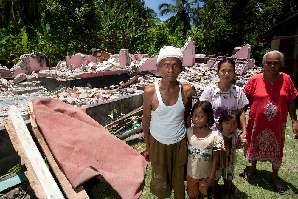Gunung Basi Village, Padam Pariaman, Western Sumatra, Indonesia, 10th October 2009:?Mrs Syamsul Bahri and her family stand outside the remians of her earthquake affected house in Gunung Basi Village following a devastating earthquake in Western Sumatra that claimed the lives of an estimated 2000 people.?Photo: Joseph Feil