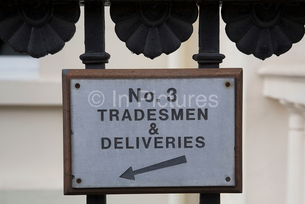 Sign for the tradesmens entrance in Belgravia London, United Kingdom. Belgravia is a district in West London in the City of Westminster and the Royal Borough of Kensington and Chelsea. It is noted for its very expensive residential properties and is one of the wealthiest districts in the world. Much of it, known as the Grosvenor Estate, is still owned by a family property company, the Duke of Westminsters Grosvenor Group.