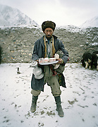Bringing tea into the guest room..Wakhis outside in Sarhad, the first village coming down from the Little Pamir. .Winter expedition through the Wakhan Corridor and into the Afghan Pamir mountains, to document the life of the Afghan Kyrgyz tribe. January/February 2008. Afghanistan