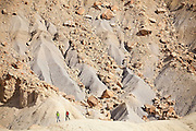 Ben Hudson and Francis Rengers, students on a geology field trip with the University of Colorado, hike along a ridge at the foot of North Caineville Mesa, Utah.