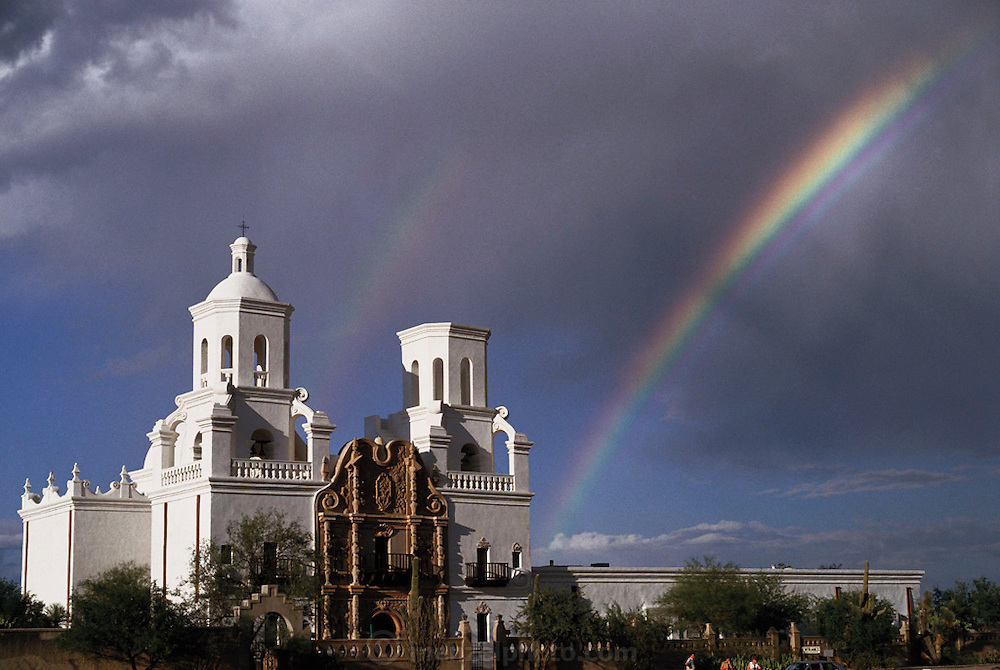 Weather: Rainbow and Mission San Xavier in Tucson, Arizona. Rainbows occur when the observer is facing falling rain but with the sun behind them. White light is reflected inside the raindrops and split into its component colors by refraction. (1986)