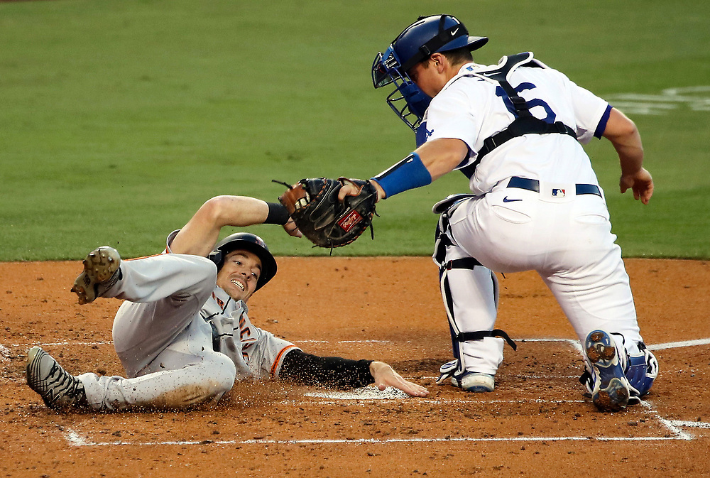 LOS ANGELES, CALIFORNIA - AUGUST 07: Mike Yastrzemski #5 of the San Francisco Giants slides into home base against Will Smith #16 of the Los Angeles Dodgers during the third inning at Dodger Stadium on August 07, 2020 in Los Angeles, California. (Photo by Katelyn Mulcahy/Getty Images)