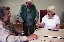 Elderly women playing game of dominoes at day centre,