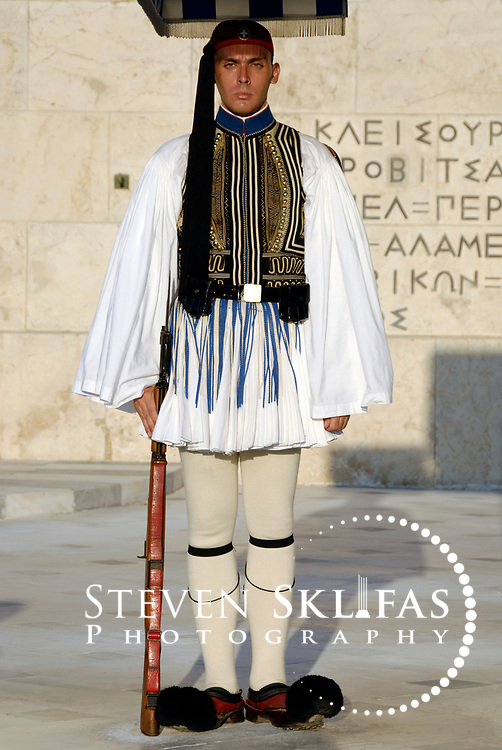 Syntagma square. Athens. Greece. View of an elite member of the Presidential ceremonial guard unit known as Evzones standing guard in front of the monument to the Unknown Soldier. The monument to the Unknown Soldier, erected in 1929-1932, depicts a relief of a dying Greek solider and is watched around the clock by Evzones standing motionless outside their sentry boxes wearing traditional dress. This guard is wearing the full dress uniform consisting of a white, bell-sleeved shirt and a white foustanella with 400 pleats (Symbolising the 400 years of Ottoman occupation). It is only worn on Sundays or important national holidays.