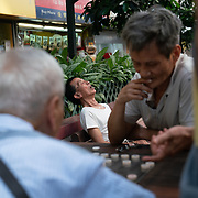 A man sleeps on a park bench while others play chess.  Hong Kong has the highest rental prices in the world.