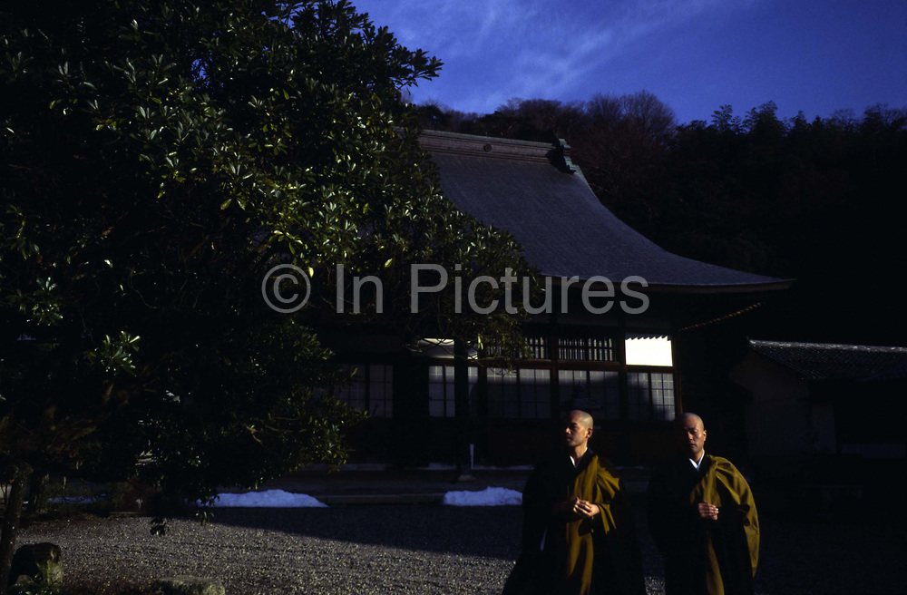 """Two Buddhist monks walk in the grounds of the Seiryu-ji Temple after meditation.<br /> In Zen Buddhism, zazen (literally """"seated meditation"""") is a meditative discipline practitioners perform to calm the body and the mind and experience insight into the nature of existence and thereby gain enlightenment (satori)"""
