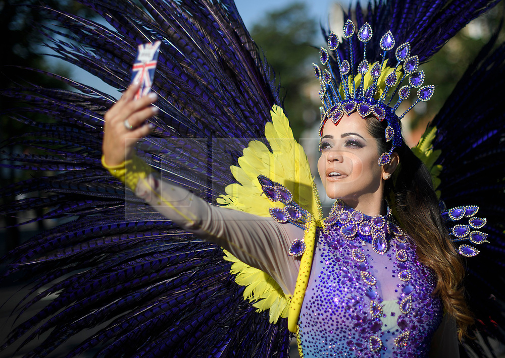 © Licensed to London News Pictures. 26/08/2019. London, UK. A woman in carnival dress enjoy Day two of the Notting Hill carnival. The two day event is the second largest street festival in the world after the Rio Carnival in Brazil, attracting over 1 million people to the streets of West London. Photo credit: Ben Cawthra/LNP