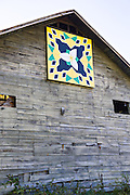 A old wooden barn decorated with a Quilt Block on the Quilt Trails near Burnsville, North Carolina. The quilt trails honor handmade quilt designs of the rural Appalachian region.