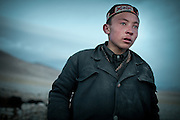 Mujaheed, grand son of the Khan, looks at the yak herd..In and around the campment of Kyzyl Qorum, campment of the former deceased Khan, Abdul Rashid Khan..Trekking with yak caravan through the Little Pamir where the Afghan Kyrgyz community live all year, on the borders of China, Tajikistan and Pakistan.
