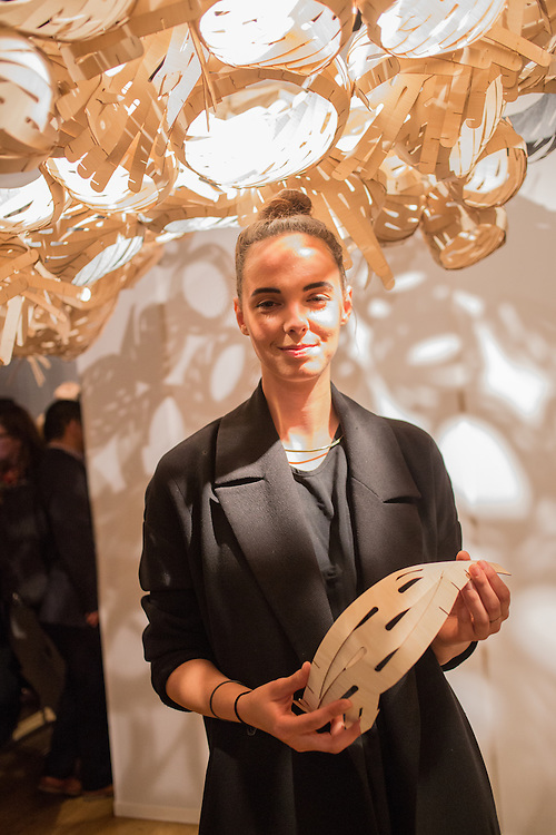 MFA interior design student Laura Alexandra Suppan holds a sample of veneer used as a basic structural element in the lighting above her. The lighting was designed by a collaboration with students from Parsons The New School for Design with help from Alpi, the suppliers of the veneer.