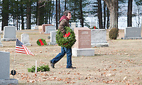 Randy Brough helps place holiday wreaths onto the graves of 455 New Hampshire veterans at the Bayside Cemetery Saturday afternoon for the Laconia Rotary Club's annual Wreaths Across America event.  (Karen Bobotas/for the Laconia Daily Sun)