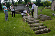 Visitors inspect the row of childrens' graves in the churchyard of St James, Cooling, Kent. Charles Dickens wrote about these graves in the opening of his famous novel Great Expectations (1860). Dickens lived nearby in Higham and referred to this row of children's tombstones now inevitably referred to as Pip's graves. Dickens pictures them as '....five little stone lozenges each about a foot and a half long which were arranged in a neat row ... and were sacred to the memory of five little brothers of mine....' In fact the Cooling graves belong to the children of two families, aged between 1 month and about a year and a half, who died in the late 18th and 19th centuries.