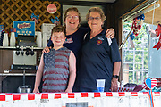 Workers at a stand selling soft drinks pose for a photo during the Independence Day parade in Millville, Pennsylvania on July 5, 2021.