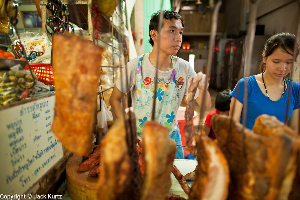09 JULY 2011 - BANGKOK, THAILAND: A pork vendor cuts up a customer's order in the Chinatown section of Bangkok, Thailand. Chinatown is the entrepreneurial hub of Bangkok, with thousands of family owned businesses selling wholesale merchandise in everything from food like rice, peanuts and meats, to dry goods like toys and shoes.  PHOTO BY JACK KURTZ