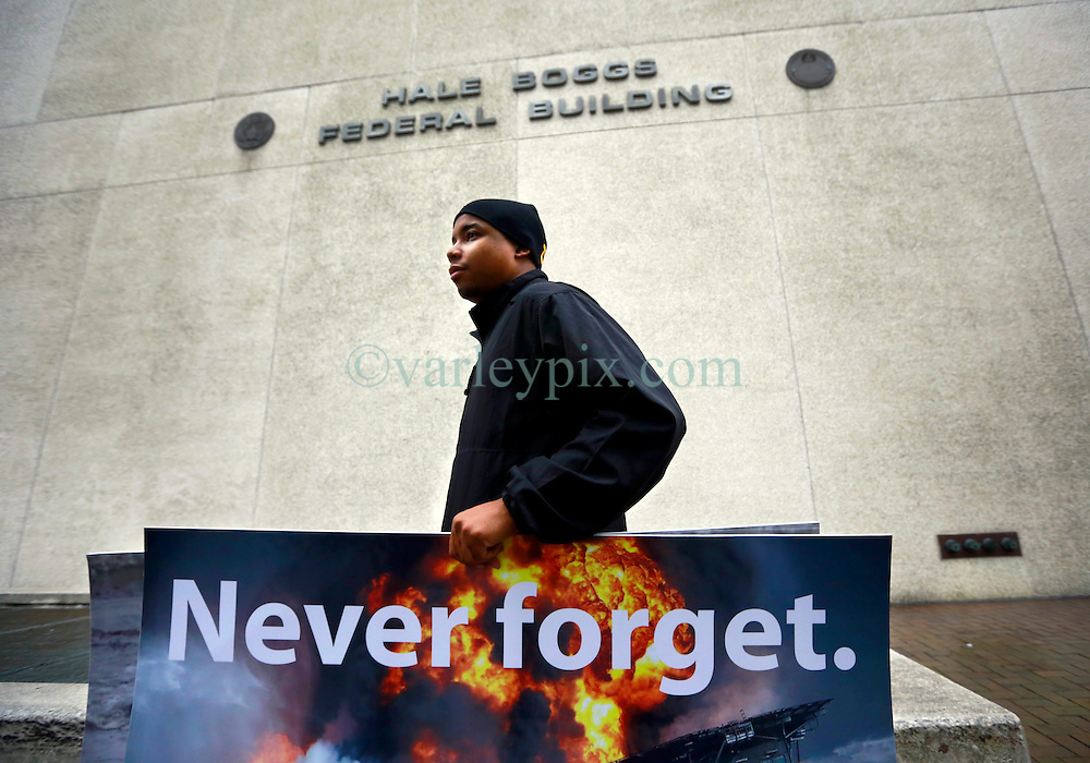 25 February 2013. New Orleans, Louisiana,  USA. .BP Trial. Protester Happy Johnson walks past the Hale Boggs Federal Courthouse in the early morning drizzle on the opening day of the BP trail  at the New Orleans Federal Courthouse..Photo; Charlie Varley.