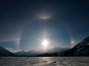 Low winter sun on a subzero day with sun dogs or parahelia, 22º halo and tangent arcs, above the frozen Slims River, Kluane Ranges, Kluane Naitonal Park, Yukon Territory, Canada