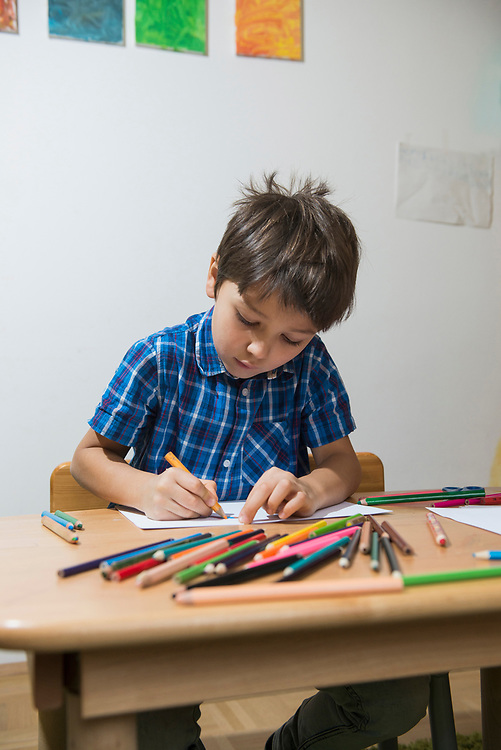Boy colouring with coloured pencils Munich, Germany