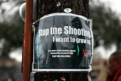 04 March 2014. New Orleans, Louisiana.<br /> 'Stop the shooting. I want to grow up.' A sign on a pole through some of the most violent streets along the early morning route for the Krewe of Zulu. On the streets of New Orleans.<br /> Photo; Charlie Varley/varleypix.com