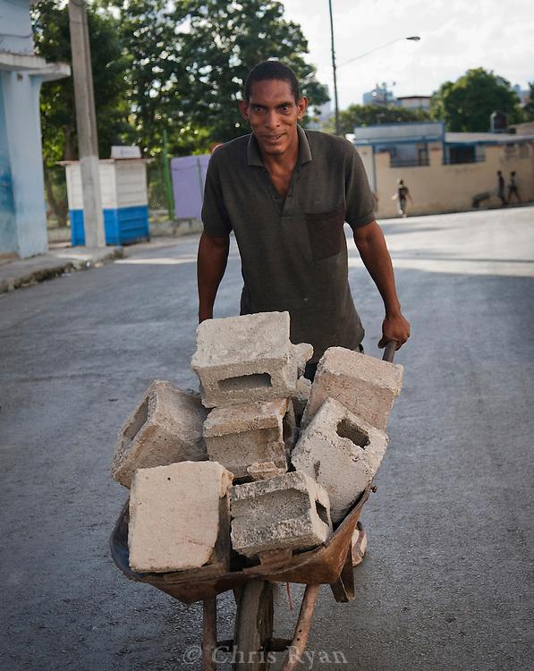 Man hauling cinderblocks in wheelbarrow, Casablanca, Cuba