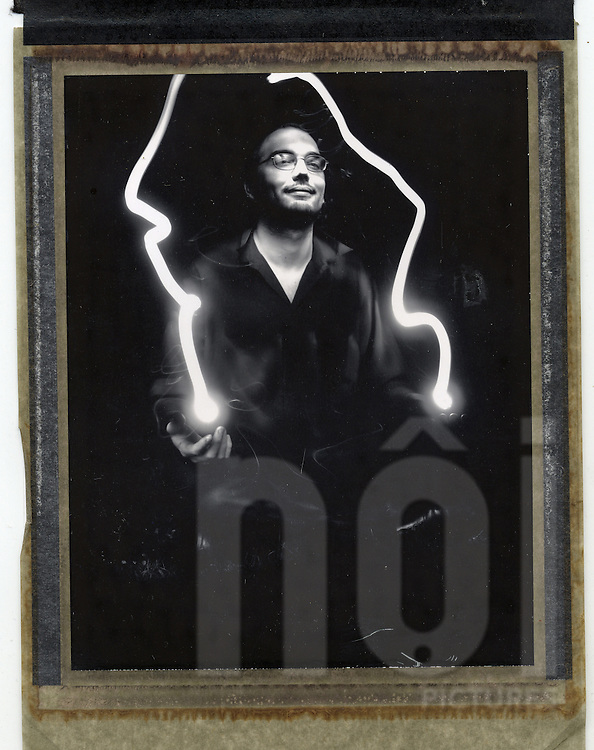 Old black and white Polaroid of a magician. Light painting is used to create the illusion of magic coming from his hands.