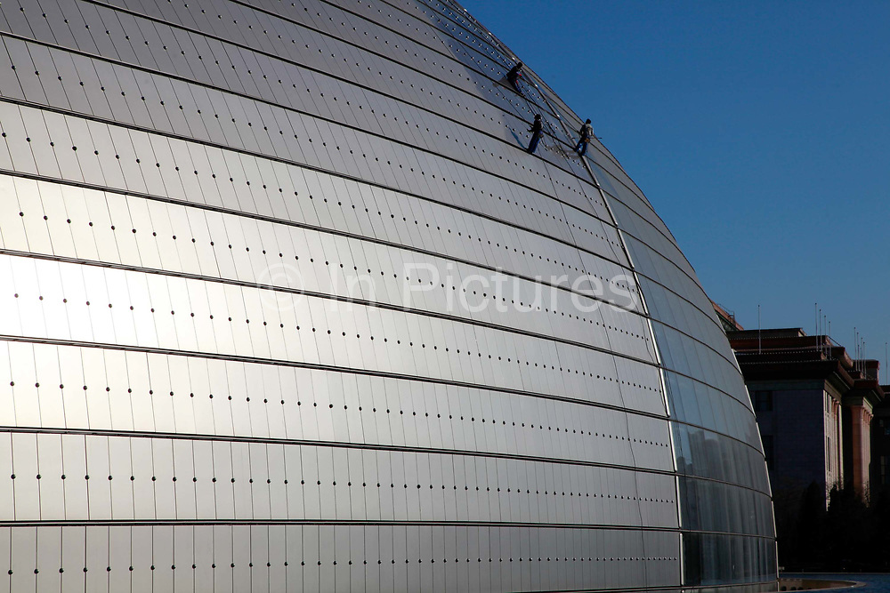 """Workers hose off dust accumulated on the titanium and glass exterior of the National Centre for the Performing Arts in Tiananmen Square in Beijing, China, on 10 December 2011.   Dubbed by locals as the """"Egg"""", the opera house was designed by French architect Paul Andreu. Construction started in December 2001 and the inaugural concert was held in December 2007, the building needs frequent cleaning as the exterior easily accumulates and shows dust and pollution."""