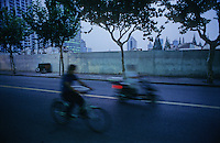 People riding on bikes and moped's in a Shanghai evening, China.